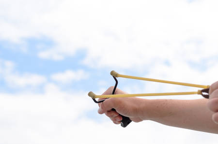 accuracy: Close up Human Hand Pulling Bands of his Stone Shooter Stick Against White and Blue Sky.