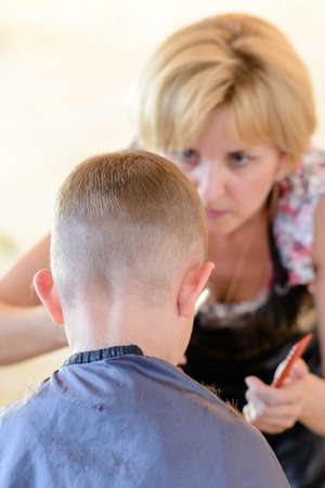trims: Attractive blond hairdresser cutting a young boys hair in a short hairstyle bending forwards as she trims the front, viewed from behind the child