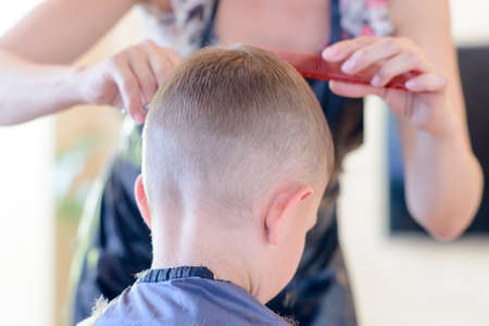 Attractive blond hairdresser cutting a young boys hair in a short hairstyle bending forwards as she trims the front, viewed from behind the child photo