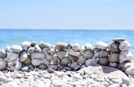 Stones stacked into a wall at the seaside on a beach strewn with pebbles against a tropical ocean backdrop Stock Photo