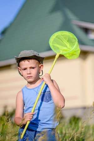 preteen boy: Waist Up Portrait of Young Boy Outdoors in Summer Standing in Field Holding Green Bug Net and Looking to the Side