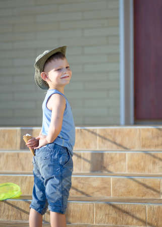 mirth: Smiling Young Boy Wearing Summer Clothes Standing Outside in front of Home with Ice Cream Cone Hidden Behind Back, Sneaky Boy with Ice Cream Moustache Hiding Ice Cream Treat