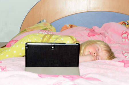 sleeping tablets: Cute Blond Little Girl Lying on her Stomach While Sleeping on her Bed with Tablet Computer on a Stand