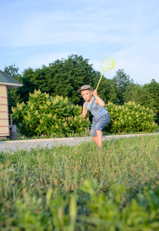 sleeveless top: Cute funny little boy wearing hat, sleeveless top and short pants, while running to catch butterflies with a net on the green lawn in a warm day of summer