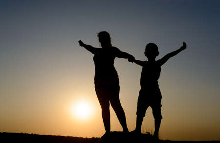 outspread: Mother and son standing holding hands on a rock with outspread arms silhouetted by the orange orb of the setting sun at dusk, with copyspace