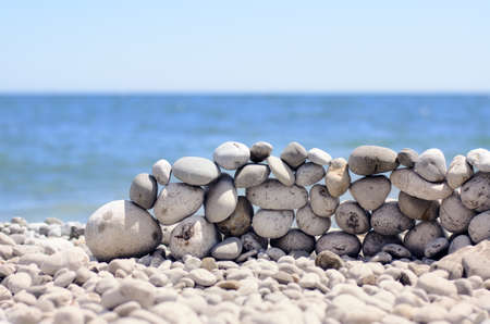 counterbalance: Stones stacked into a wall at the seaside on a beach strewn with pebbles against a tropical ocean backdrop Stock Photo