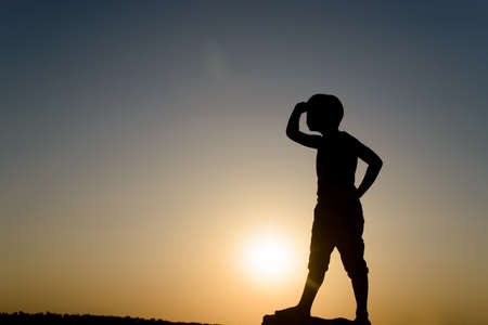 young boy: Silhouette of Young Boy Searching and Looking into the Distance with Hand Shielding Eyes, Backlit By Late Day Sun with Copy Space Stock Photo