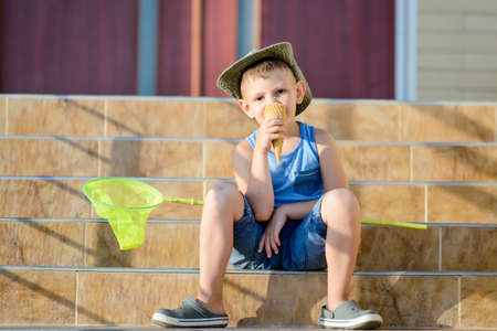 mouthful: Young Boy with Bug Net Enjoying Ice Cream on Front Steps of Home Sitting in Bright Summer Sunshine