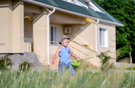 poised: Little boy catching insects with a net in the long spring grass outside his house on a sunny day Stock Photo