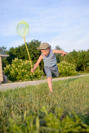 running pants: Cute funny little boy wearing hat, sleeveless top and short pants, while running to catch butterflies with a net on the green lawn in a warm day of summer