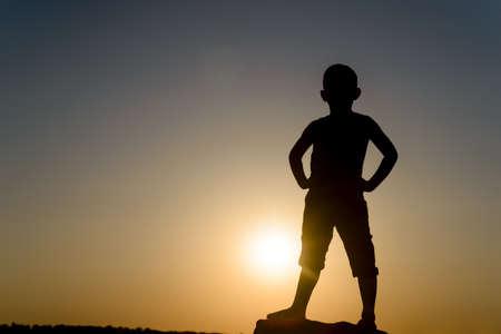 Silhouet van Jonge Zekere en krachtige Boy stond met de handen op de heupen, verlicht door late dag zon met kopie ruimte Stockfoto