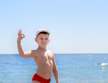 niño sin camisa: Muchacho joven hermoso en la playa en un día soleado de verano, que muestra bien muestra de la mano mientras guiño su ojo en la cámara.