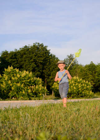 short pants: Cute funny little boy wearing hat, sleeveless top and short pants, while running to catch butterflies with a net on the green lawn in a warm day of summer