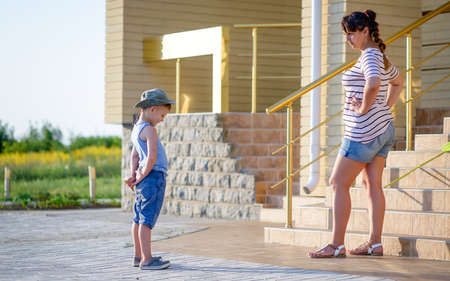 disobedient: Angry Mother Scolding Son in front of Home - Young Boy Hiding Ice Cream Cone Behind Back and Getting into Trouble