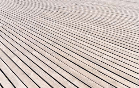receding: Background texture of wooden decking with parallel planks with gaps in a receding perspective, horizontal full frame view