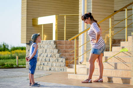 disobedient child: Young Boy Hiding Ice Cream Cone Behind Back While Being Scolded by Angry Mother with Hands on Hips in front of Home Stock Photo