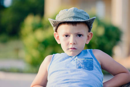 preteen boys: Portrait of Serious Young Boy Wearing Tank Top and Hat Leaning Back and Staring at Camera Outdoors