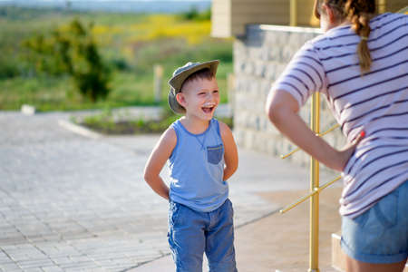 disrespectful: Young Boy with Ice Cream Moustache Standing with Hands Behind Back and Laughing in front of Angry Mother Standing with Hands on Hips Outdoors