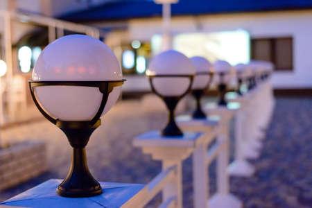 Row of Unlit Globe Lights on Stone Patio Outdoors at Dusk
