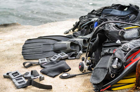 fins: Pile of Scuba Diving Equipment Including Fins and Weights Drying on Coastal Dock near Water Stock Photo