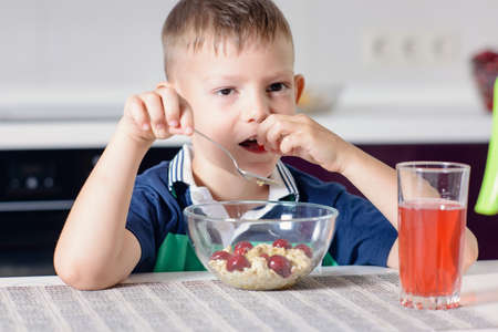disinterested: Young Boy Having Breakfast at Kitchen Table, Enjoying Bowl of Oatmeal Cereal with Cherries on Top and Glass of Red Juice Stock Photo