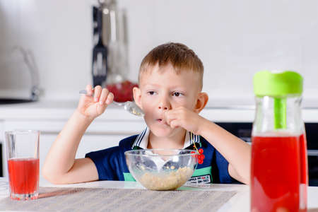 uninterested: Young Blond Boy Picking at Oatmeal Cereal in Bowl at Breakfast Time While Sitting at Kitchen Table with Glass of Red Juice