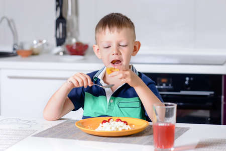 mouthful: Young Blond Boy Eating Plate of Cheese and Fruit with Spoon While Sitting at Kitchen Table