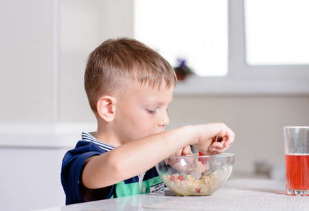 disinterested: Young Blond Boy at Kitchen Table Eating Bowl of Oatmeal Cereal for Breakfast with Glass of Red Juice Stock Photo
