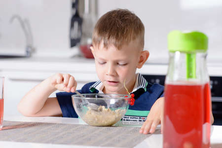 expressionless: Young Blond Boy at Kitchen Table Eating Bowl of Oatmeal Cereal for Breakfast with Glass of Red Juice Stock Photo