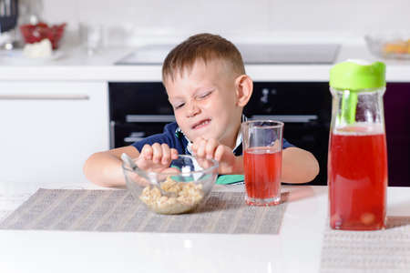 spoilt: Young Boy Pushing Bowl of Breakfast Oatmeal Cereal Away in Protest While Sitting at Kitchen Table with Glass of Red Juice