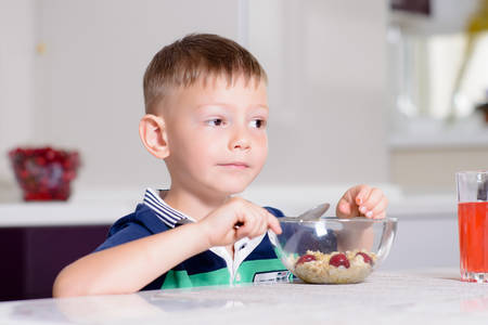 little boys: Young Boy Having Breakfast at Kitchen Table, Enjoying Bowl of Oatmeal Cereal with Cherries on Top and Glass of Red Juice Stock Photo