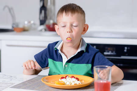 expressionless: Young Blond Boy with Mouth Stuffed Full Eating Cheese and Fruit Off Orange Plate While Sitting at Kitchen Table with Glass of Red Juice