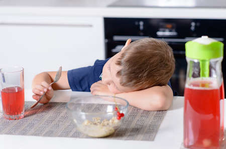 playing with spoon: Bored young boy waiting for his meal as he sits at a table in the kitchen resting his head on his arm and playing with his spoon Stock Photo