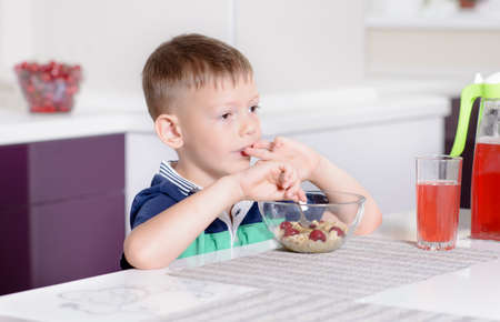 uninterested: Young Boy Having Breakfast at Kitchen Table, Enjoying Bowl of Oatmeal Cereal with Cherries on Top and Glass of Red Juice Stock Photo