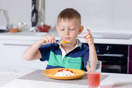 expressionless: Young Blond Boy Eating Plate of Cheese and Fruit with Spoon While Sitting at Kitchen Table