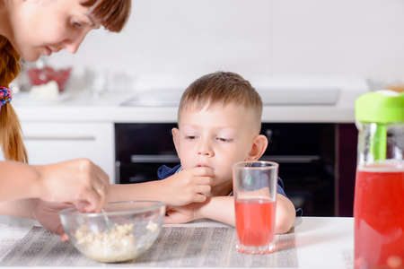 disinterested: Mother serving her young son his lunch as he sits at a table in the kitchen, close up with focus to the small boy