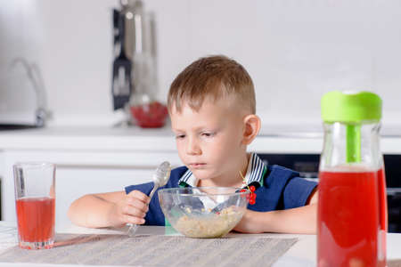 unemotional: Young Blond Boy at Kitchen Table Eating Bowl of Oatmeal Cereal for Breakfast with Glass of Red Juice Stock Photo