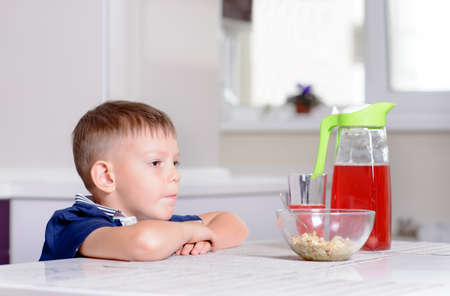 unemotional: Young Serious Blond Boy Sitting at Kitchen Table Contemplating Bowl of Oatmeal Cereal and Red Juice at Breakfast