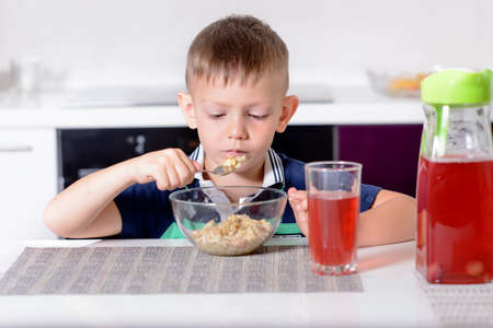 unemotional: Young Boy Having Breakfast at Kitchen Table, Enjoying Bowl of Oatmeal Cereal with Cherries on Top and Glass of Red Juice Stock Photo