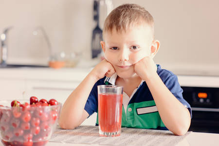 leaning on elbows: Young Boy Sitting at Kitchen Table Leaning on Elbows and Smiling at Camera with Glass of Red Juice and Bowl of Ripe Cherries