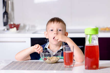 unemotional: Young Boy Eating Cherries Off Top of Oatmeal Cereal at Breakfast While Sitting at Kitchen Table, with Glass of Red Juice