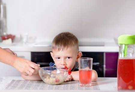 unemotional: Mother serving her young son his lunch as he sits at a table in the kitchen, close up with focus to the small boy