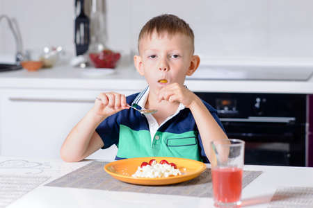 uninterested: Young Blond Boy Eating Plate of Cheese and Fruit with Spoon While Sitting at Kitchen Table