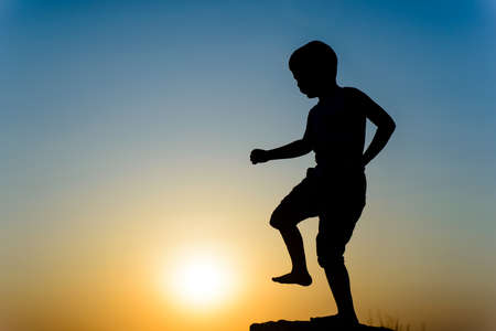 Little boy silhouetted on a wall or rock kicking the fiery orange orb of the setting sun with his foot, with copyspace Stock Photo