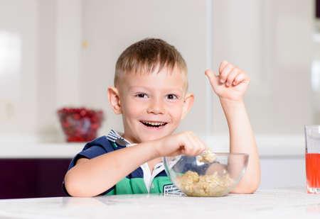 comiendo cereal: Muchacho joven sonriente Dar entusiasta pulgares para arriba mientras que come el desayuno de cereal de avena en la mesa de la cocina