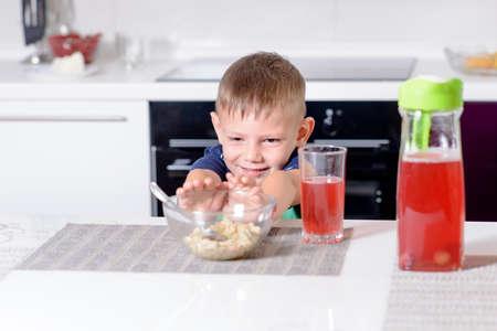 niño empujando: Muchacho joven Empujar tazón de desayuno de avena Cereal lejos en la protesta mientras estaba sentado en mesa de la cocina con vaso de jugo rojo
