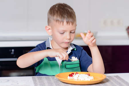 little boys: Young Blond Boy Eating Plate of Cheese and Fruit with Spoon While Sitting at Kitchen Table