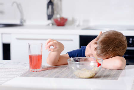 disinterested: Young boy waiting patiently for his lunch resting his head on his arm on the kitchen table with a bored expression