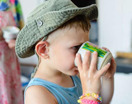 sediento: Cierre de Thirsty blanco lindo muchacho joven con sombrero de vaquero, Agua Potable en un cristal serio Foto de archivo