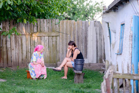 meaningful: Young Woman Dressed in Modern Clothes Sitting Outdoots Having Meaningful Conversation with Mother or Grandmother in Traditional European Clothing in Yard of Rustic Shack in Rural Area